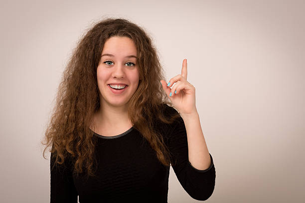 Teenage Girl Is Having A Brilliant Idea Studio photo of a ginger girl with long curly hair having a eureka moment pointing upwards isolated against a grey background. aha stock pictures, royalty-free photos & images