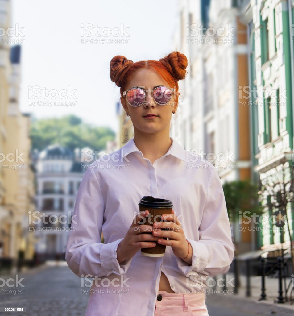 b469a4ad7d0d teenage girl is traveling down the street in a sunny morning. girl is drinking  coffee