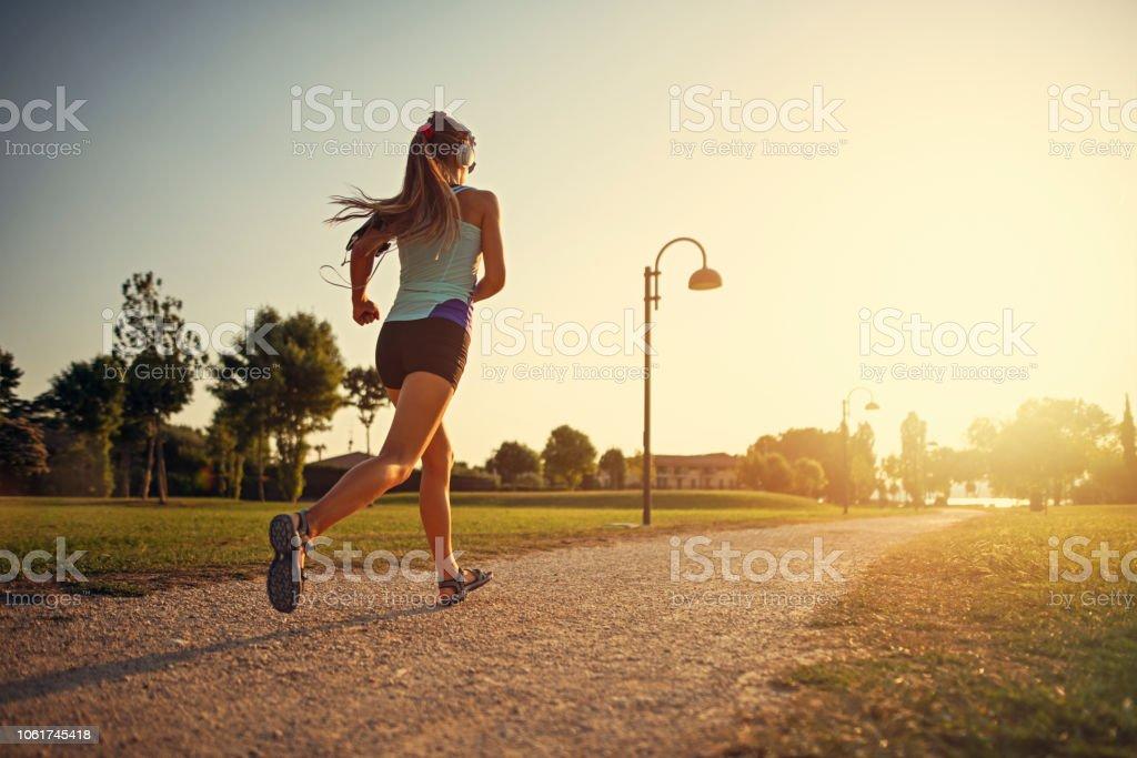 Teenage girl jogging in city park - Foto stock royalty-free di Abbigliamento sportivo