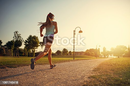 Teenage girl jogging in city park. Sunny summer day sunset. Nikon D850