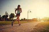 Teenage girl jogging in city park. Sunny summer day sunset. Nikon D850