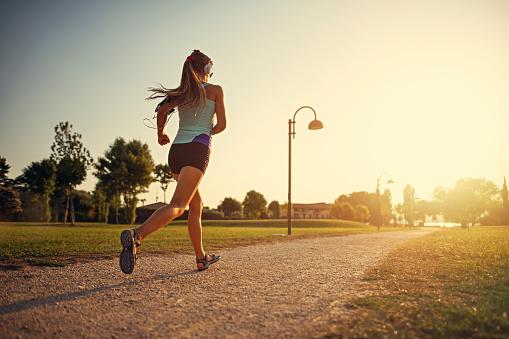 Teenage Girl Jogging In City Park - Fotografie stock e altre immagini di Abbigliamento sportivo
