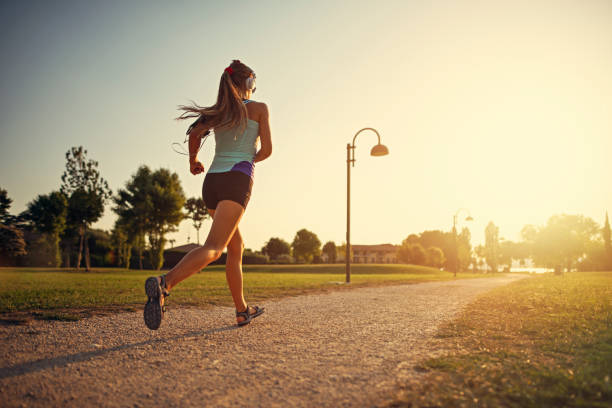 teenage girl jogging in city park - jogging stock pictures, royalty-free photos & images
