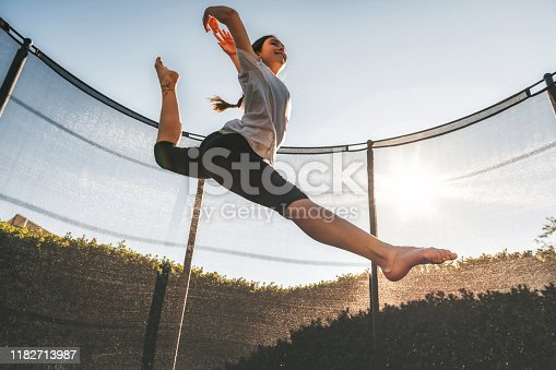 teenage girl jumping high on trampoline under blue sky