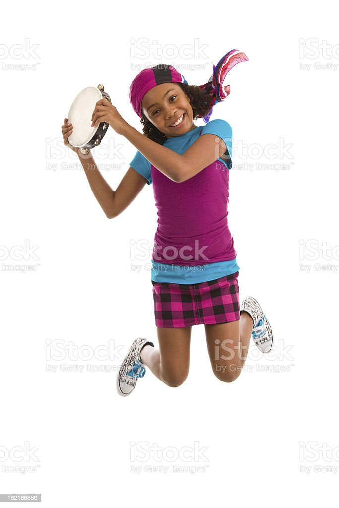 Teenage girl jumping in air holding tambourine royalty-free stock photo