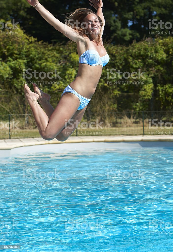 Teenage girl jumping into swimming pool royalty-free stock photo