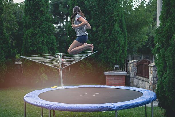 teenage girl jumping on trampoline - gartentrampolin stock-fotos und bilder