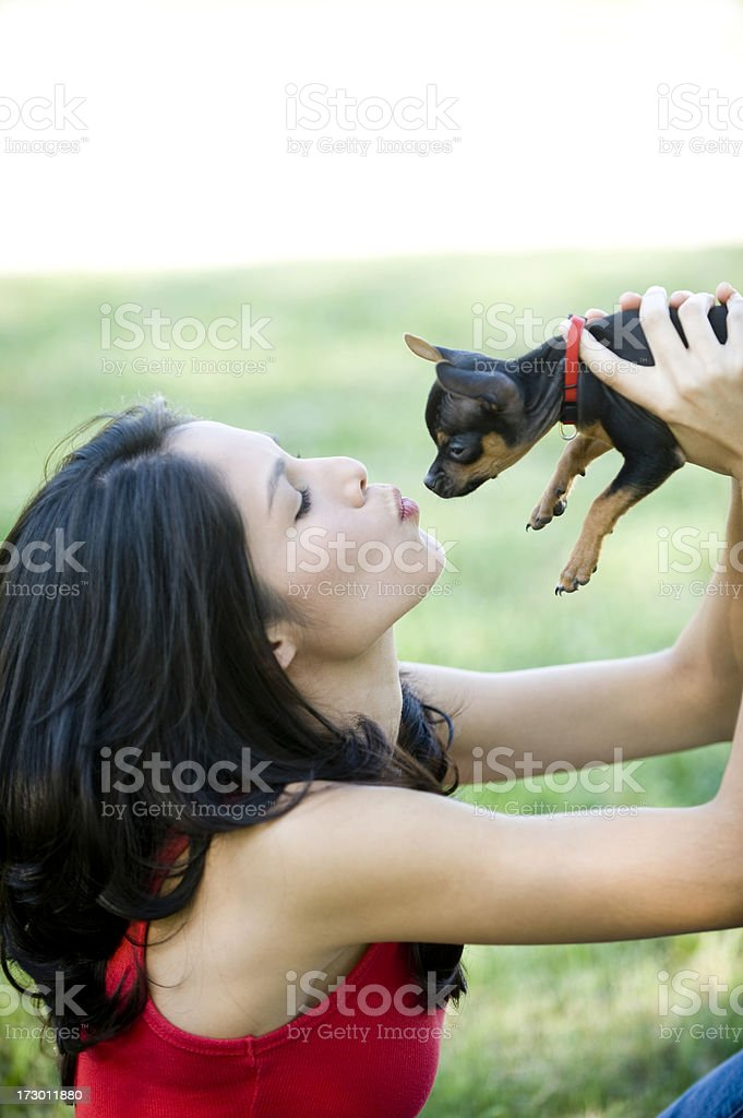Teenage girl kissing chihuahua, side view royalty-free stock photo