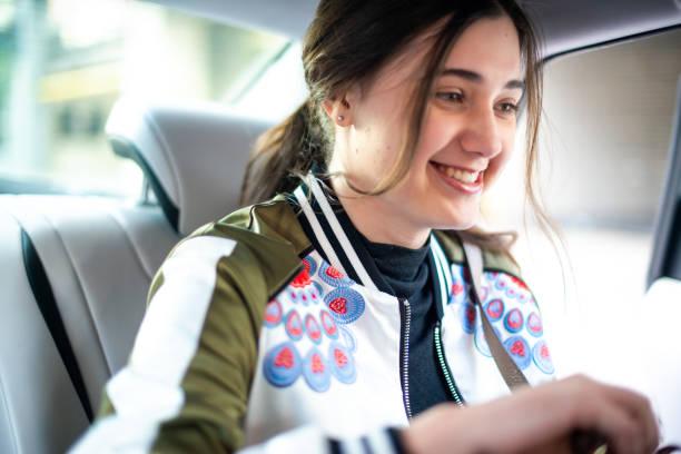 teenage girl laughing in the back seat of a car - pila a idrogeno foto e immagini stock