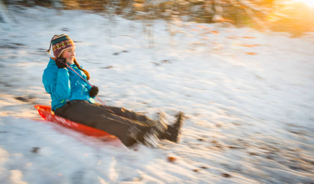 Teenage girl laughing riding sledge on snow at winter sunset stock photo