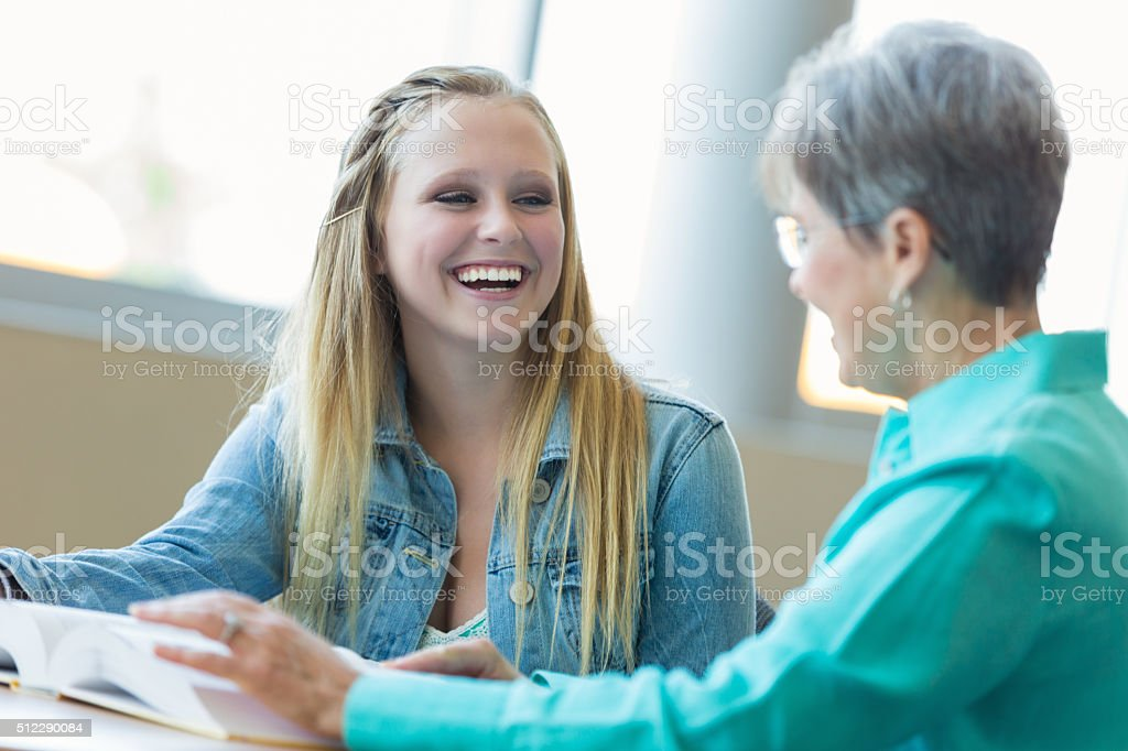 Teenage girl laughs with teacher in school library stock photo