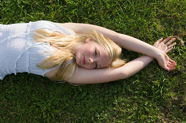 teenage girl laying in grass - england stock photos and pictures