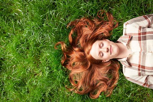 Teenage girl laying in grass