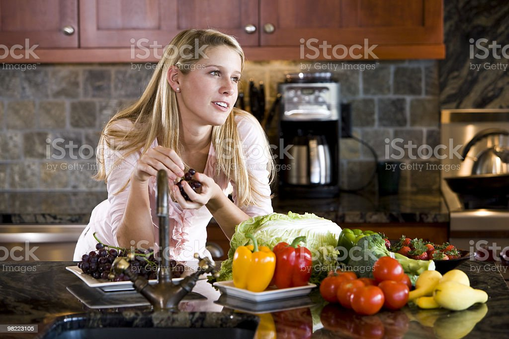 Teenage girl leaning on kitchen counter thinking royalty-free stock photo