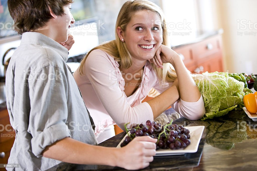 Teenage girl leaning on kitchen counter with brother royalty-free stock photo