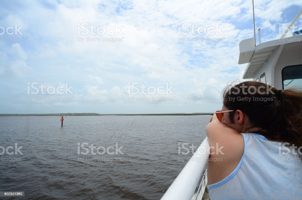 Teenage girl leaning on ship handrail and looking out to sea stock photo