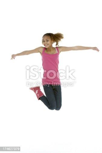 Studio Shot Of Teenage Girl Leaping In the Air
