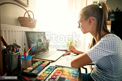 Teenage girl learning painting from YouTube. The girl is watching a painting techniques tutorial on her laptop at home. Nikon D850