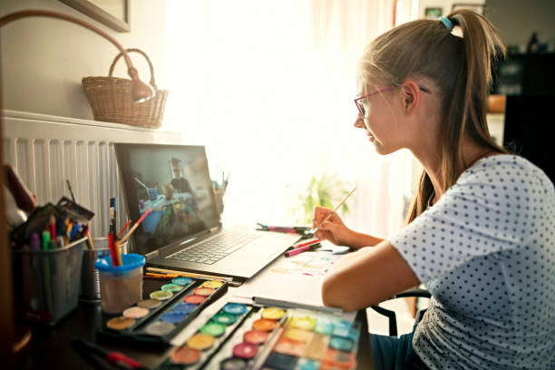 Teenage girl learning painting from YouTube stock photo