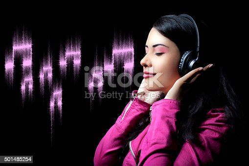 Attractive woman with headphone listening to music with color equalizer in background.