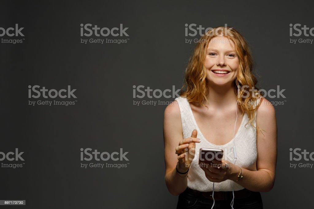 Teenage girl listening to music on her phone stock photo