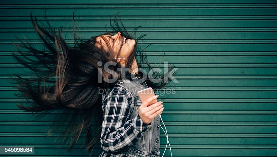 istock Teenage girl listening to the music and shaking head 545098584