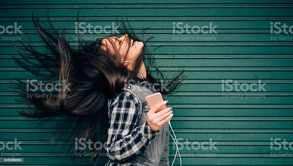 Teenage girl listening to the music and shaking head stock photo