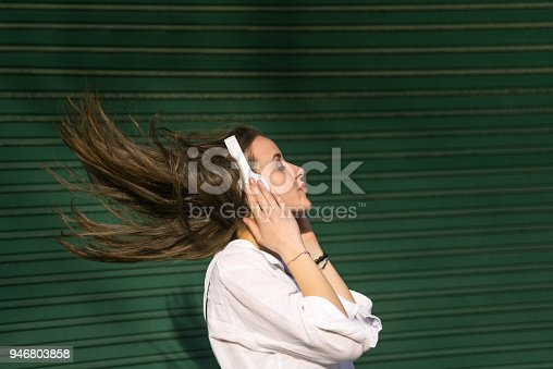 545098584 istock photo Teenage girl listening to the music and shaking head 946803858