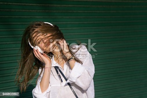 545098584 istock photo Teenage girl listening to the music and shaking head 946803862