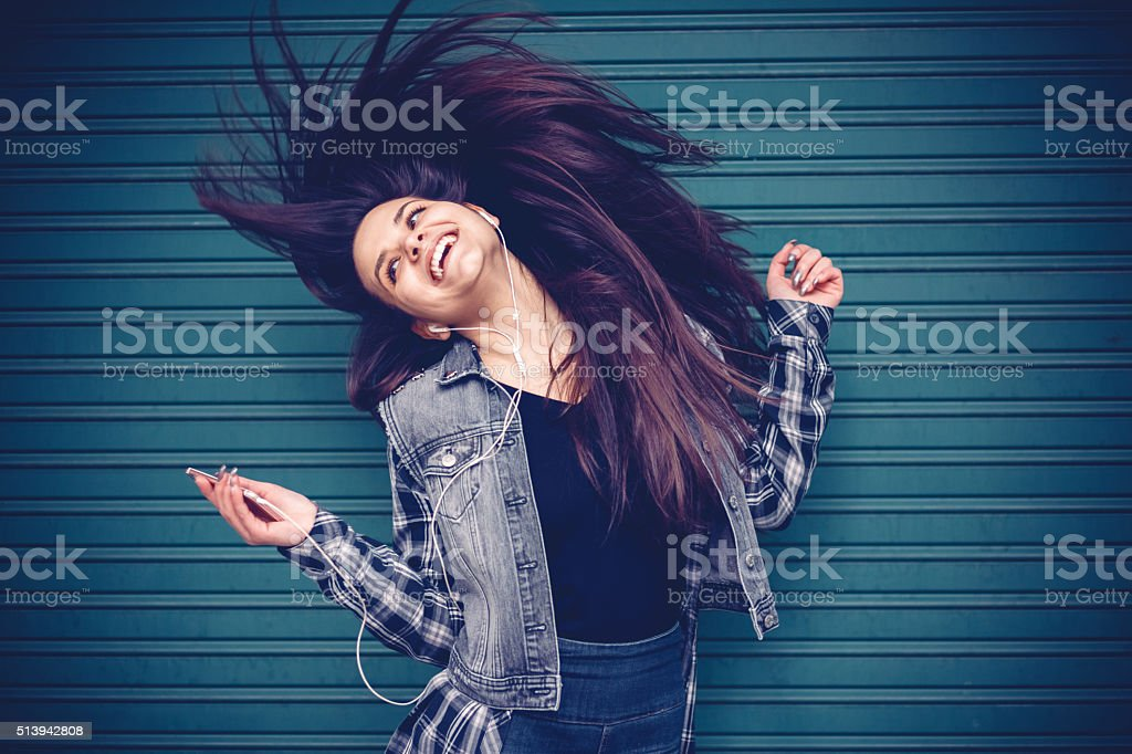 Teenage girl listening to the music and tossing hair stock photo