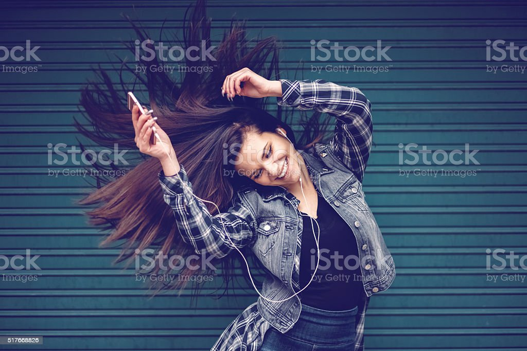 Teenage girl listening to the music and waving hair stock photo