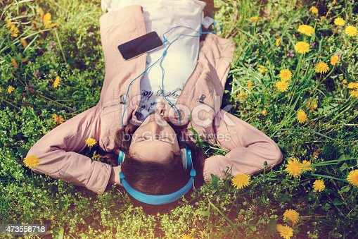 623358818 istock photo Teenage girl listening to the music in the park 473558718