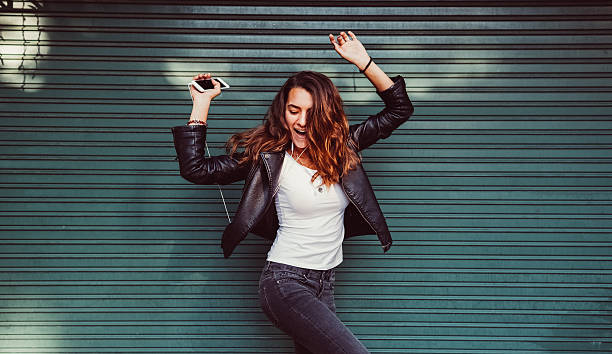 Teenage girl listening to the music Happy girl enjoying the music and dancing leather jacket stock pictures, royalty-free photos & images