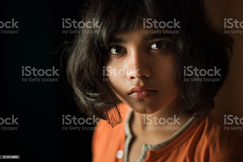 Teenage girl looking at camera with blank expression. stock photo