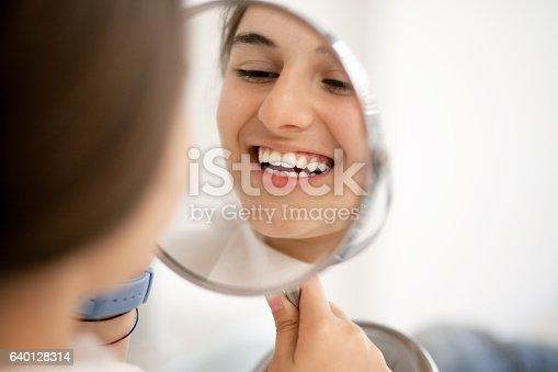 Cute teenage girl looking at her teeth in the mirror