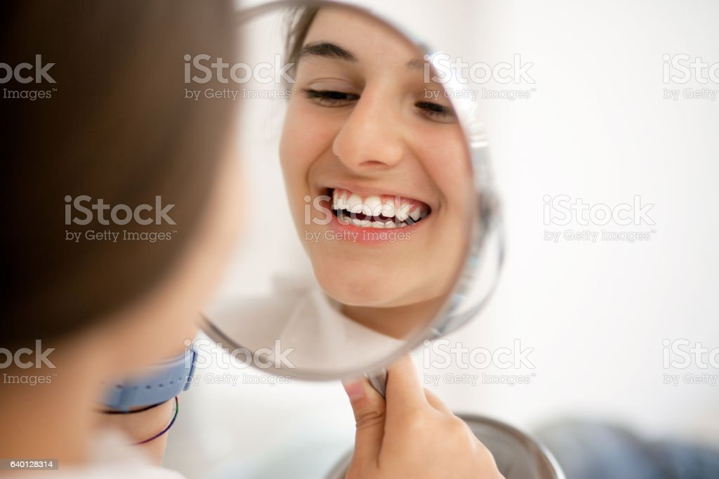 Teenage girl looking at her teeth in the mirror stock photo