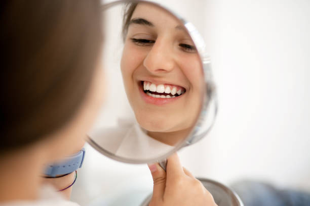 Teenage girl looking at her teeth in the mirror stock photo