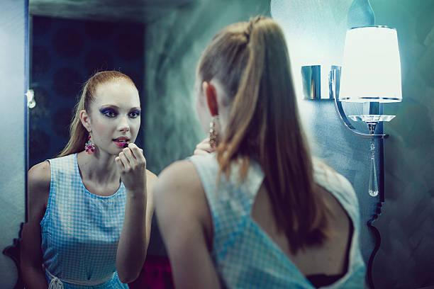 teenage girl looking at mirror applying make-up - anzieh nacht stock-fotos und bilder