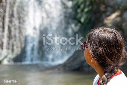 teenage girl looking at the waterfall