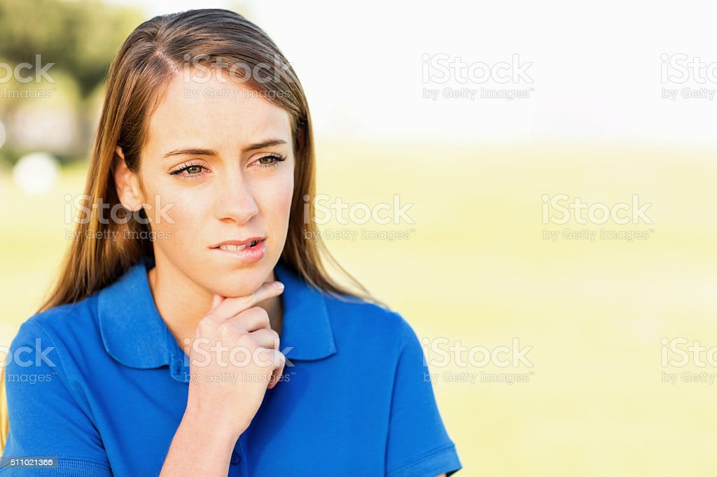 Teenage Girl Looking Away While Biting Lips At Park stock photo