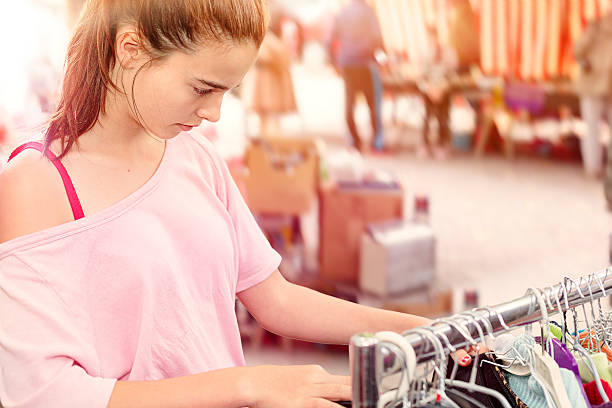 teenage girl looking for clothes at a flea market stock photo