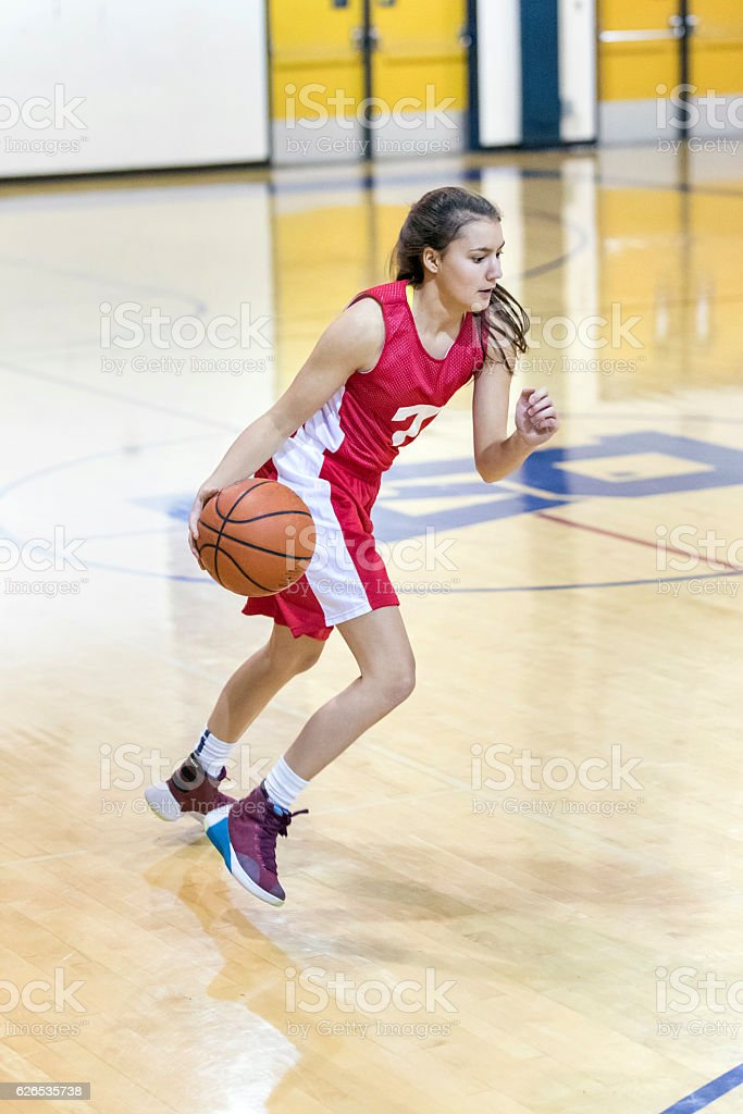 Teenage girl looking intense as she dribbles down court stock photo