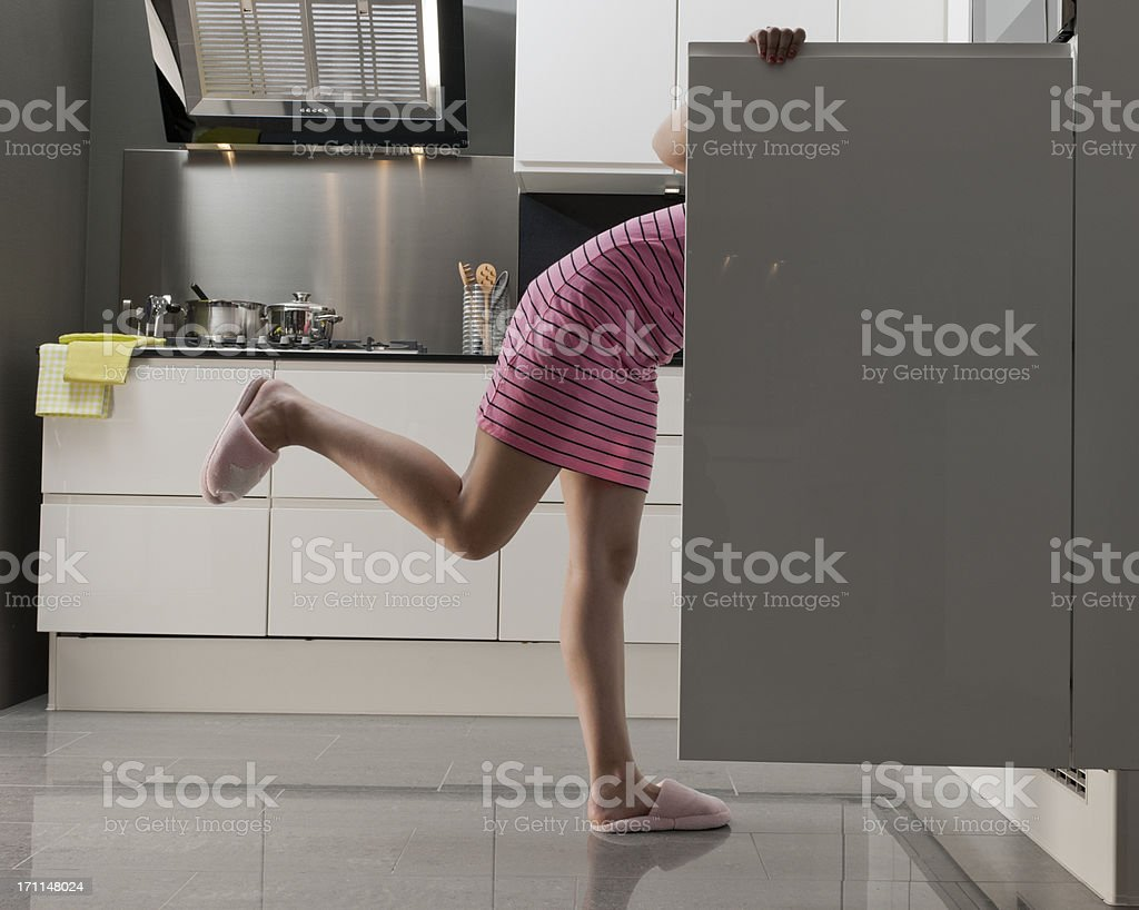 teenage girl looking into refrigerator for midnight snack stock photo