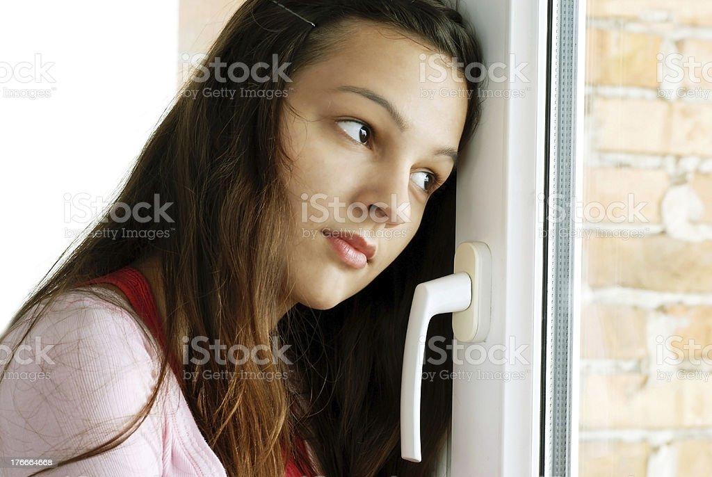 Teenage girl looking out window royalty-free stock photo