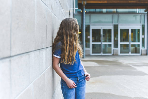 Teenage girl looking over her shoulder while leaning against a brick wall. The image displays a teenage girl leaning against a school wall all alone as she glances over her shoulder. suicide stock pictures, royalty-free photos & images