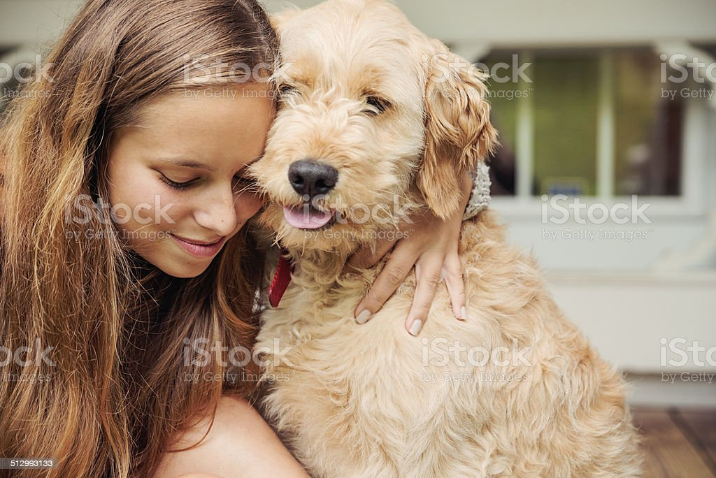 Teenage girl lovingly hugging her Goldendoodle dog on porch. stock photo