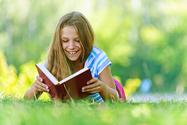 teenage girl lying on grass and read book stock photo