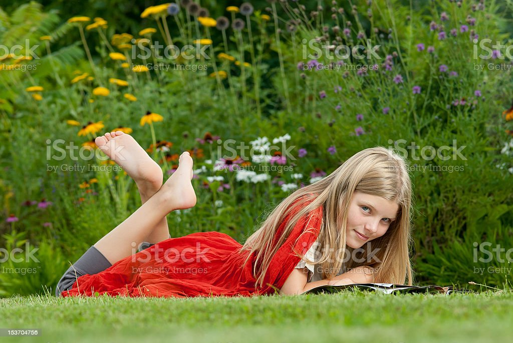 Teenage girl lying on grass and reading a magazine. stock photo