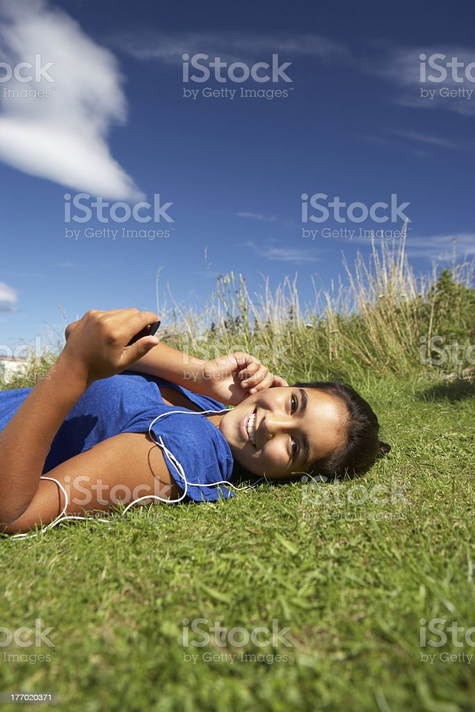 Teenage girl lying on grass with mp3 player royalty-free stock photo