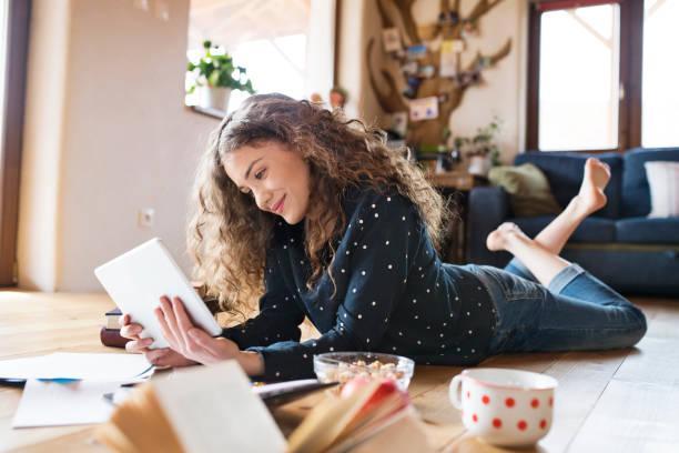 Teenager-Mädchen auf dem Boden halten Tablet, Studium – Foto